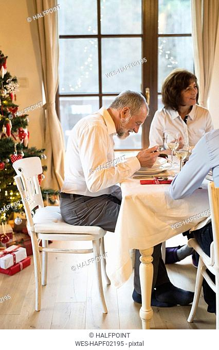 Senior man with family dining at Christmas dinner table