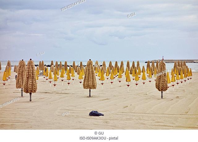 Rows of folded beach umbrellas on beach, Pescara, Abruzzo, Italy