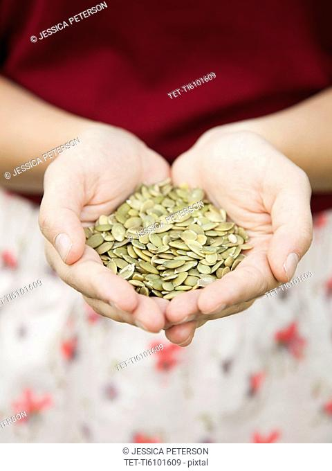 Mid-section of woman holding pumpkin seed