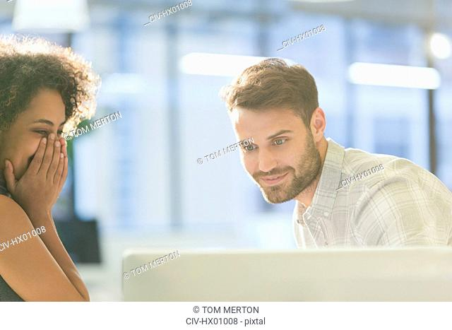 Laughing businesswoman and businessman working at computer in office