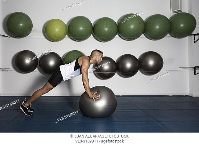 Side view of focused strong man in sportswear training with medicine ball in modern gym