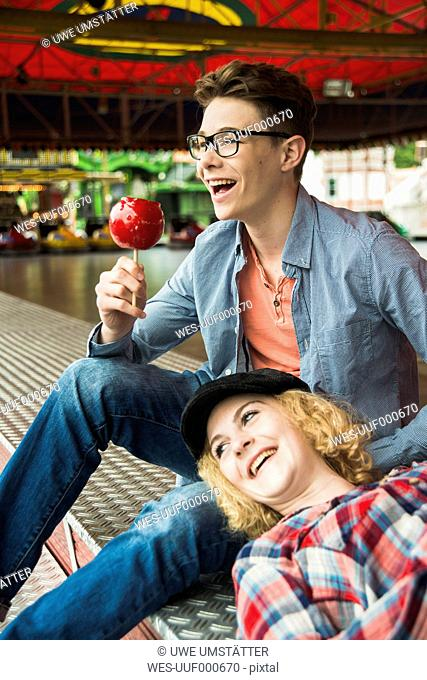 Portrait of happy teenage couple with candied apple at fun fair