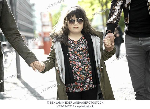 daughter holding hands of parents walking in city