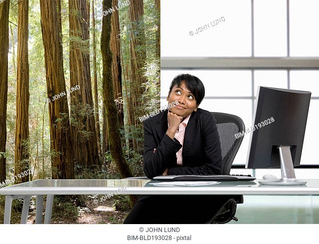 Mixed race businesswoman daydreaming in office