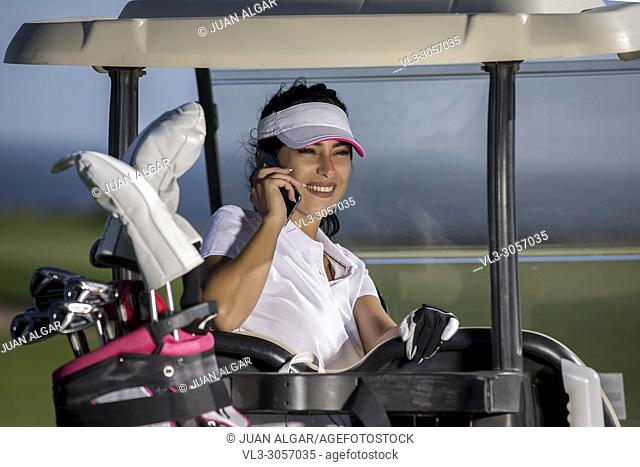 Stylish brunette in cap and white shirt having phone call sitting inside of golf buggy on field
