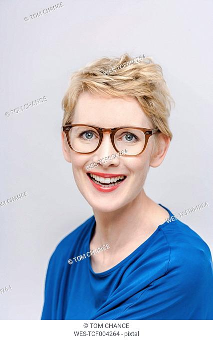 Portrait of smiling blond woman wearing glasses in front of grey background
