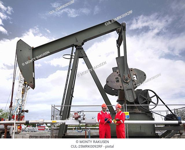 Two workers in front of oil well pump