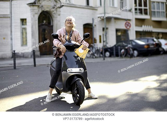 Woman on motor scooter, holding city tour guide map, in Berlin, Germany