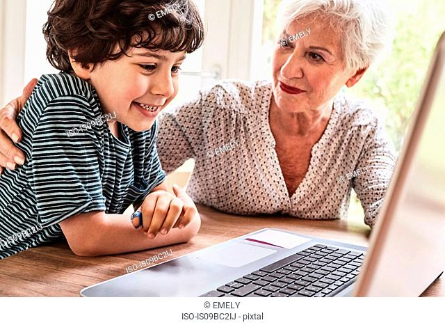 Grandmother and grandson sitting at table, using laptop