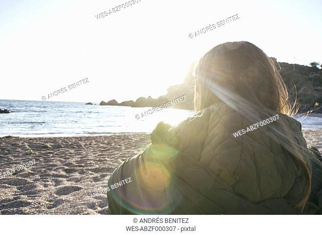 Young woman at the beach looking at sea