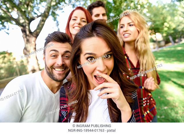 Group of friends taking selfie in urban background. Five young people wearing casual clothes