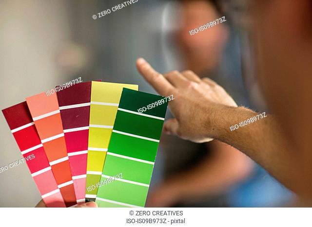 Man holding colourful paint swatches, close-up