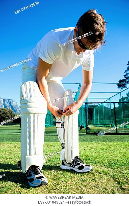 Cricket player wearing kneepad while standing on grassy field