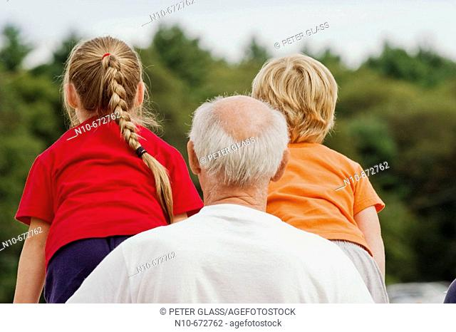 Grandfather holding onto his blond granddaughter and grandson who are standing on a fence