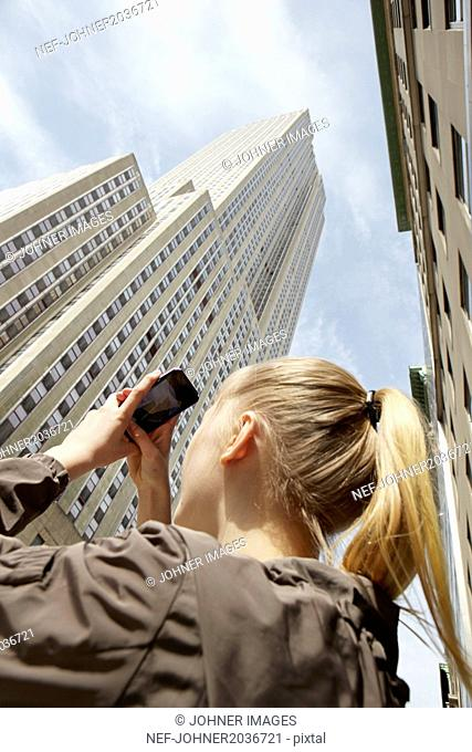 Young woman taking photo of skyscraper with her smartphone