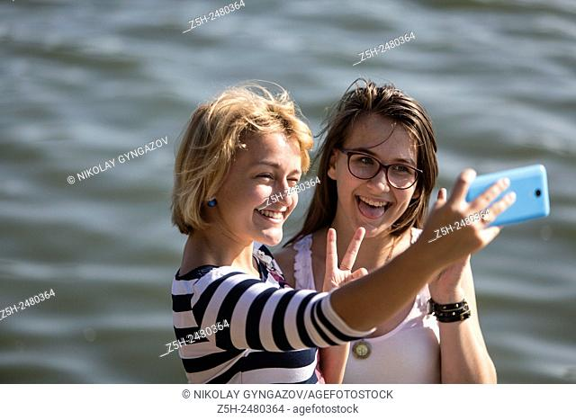 Russian Federation. Two girls are photographed on the river