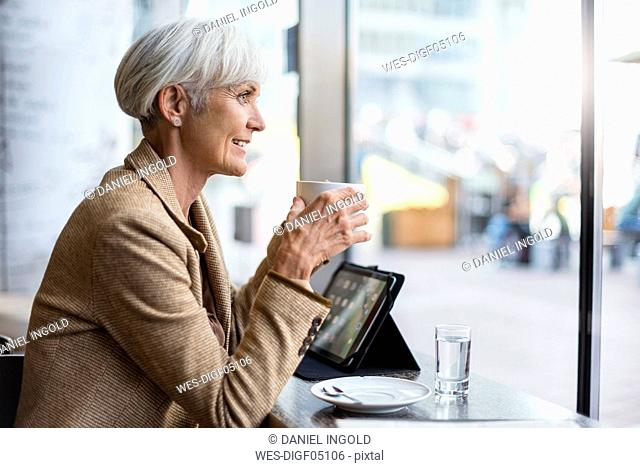 Smiling senior businesswoman with tablet in a cafe