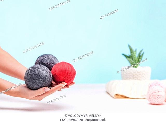 The balls of wool and female hands on blue studio background