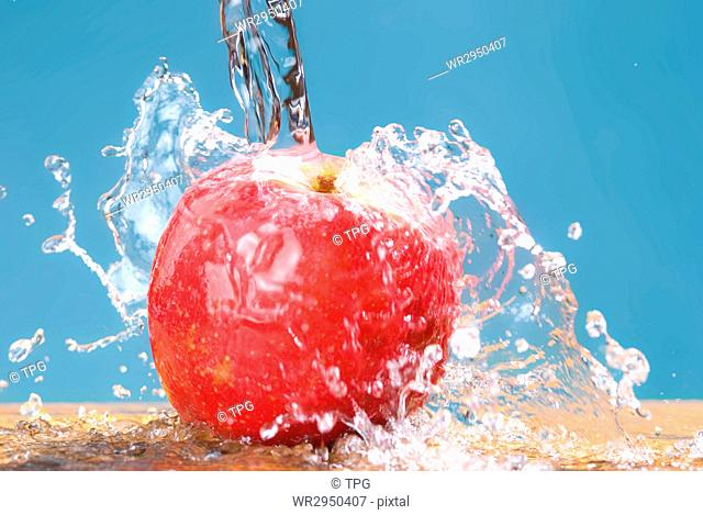 frozen splash drop on apple, cool water on blue background
