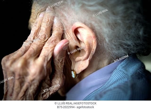 Portrait of a centennial woman in a elderly people home, hand covering her face
