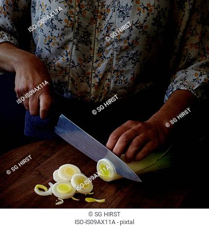 Cropped view of woman slicing leeks with kitchen knife