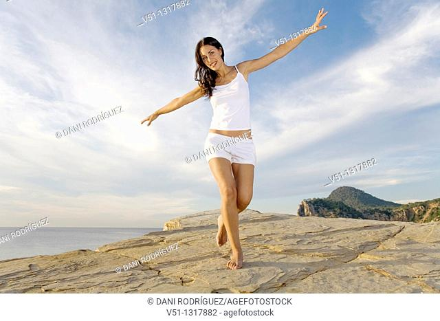 Brunette palyful woman in a cliff in Ibiza, Balearic Islands