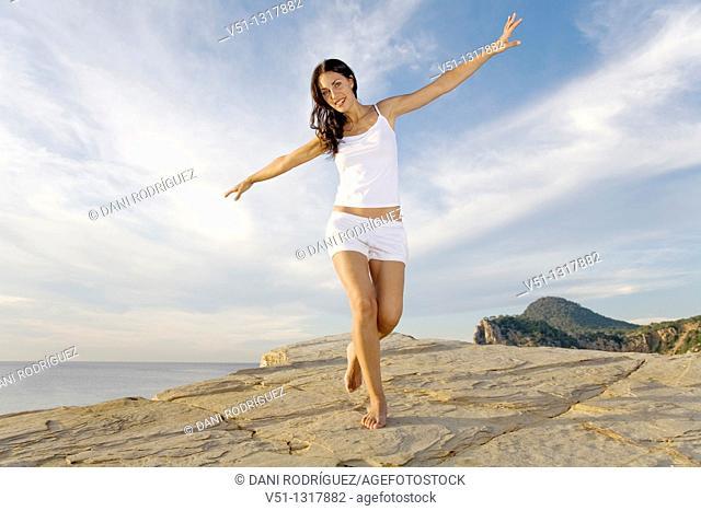 Brunette palyful woman in a cliff in Ibiza, Balearic Islands