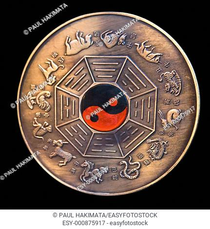 Lunar calendar depicted in a bronze medallion with a red and black ying yang in the middle, isolated on black
