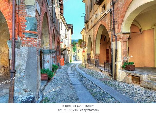 Narrow paved street among vintage brick houses in town of Avigliana, northern It