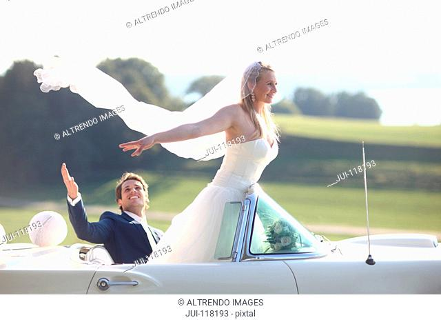 Bride And Groom In Open Top Classic Car On Wedding Day