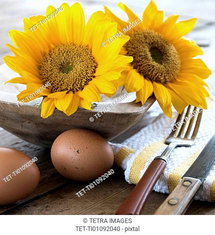 Sunflowers and eggs on table