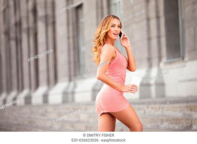 A pretty woman in a pink dress using mobile phone and holding a take away coffee