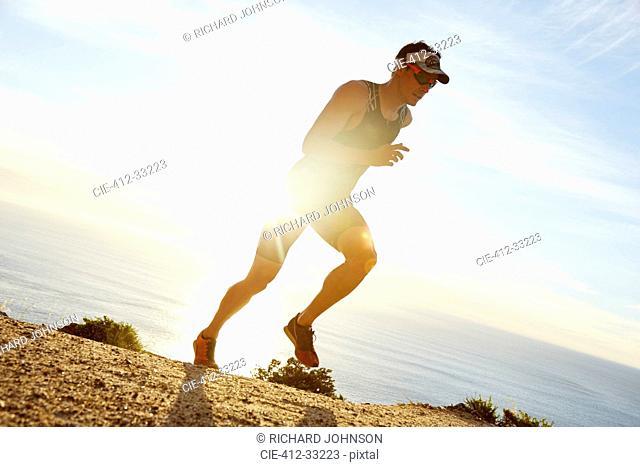 Male triathlete runner running along ocean