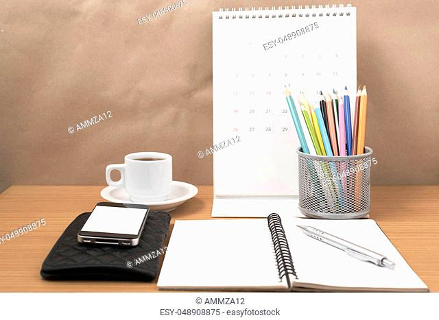 office desk: coffee with phone, wallet, calendar, color pencil box, notepad on wood background