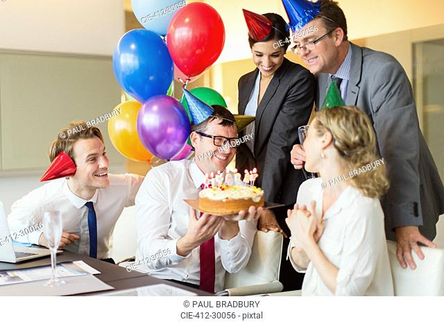 Colleagues presenting businesswoman with birthday cake in conference room