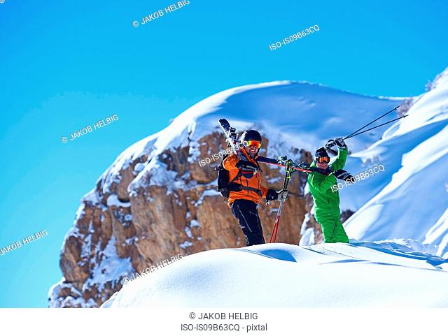 Two male skiers trudging up snow covered ridge, Aspen, Colorado, USA