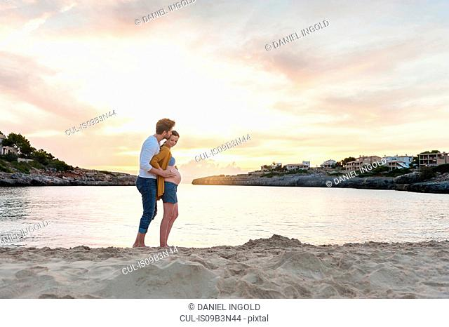 Pregnant woman and man, standing together on beach, man touching woman's stomach