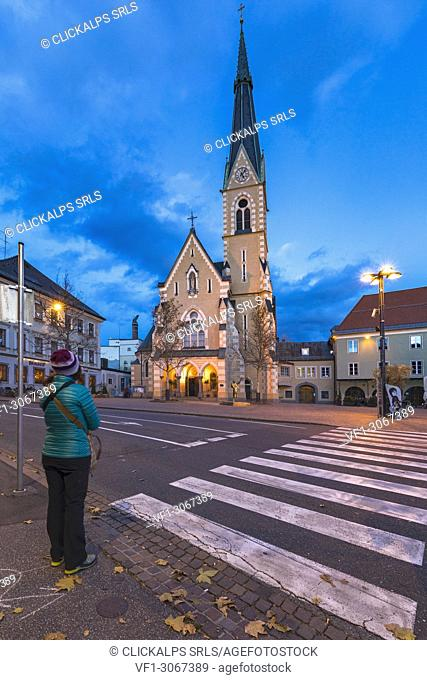 A girl in front of the Church of St. Nicholas in Villach (Carinthia, Austria, Europe)