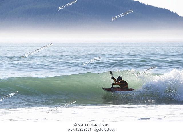 Person kayaking surfing along the Kenai Peninsula Outer Coast, South-central Alaska; Alaska, United States of America