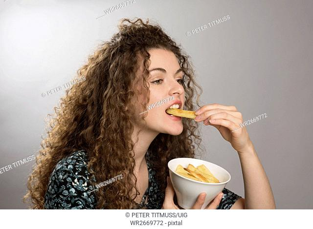 Portrait of a Teenager Eating A Bowl Of Chips