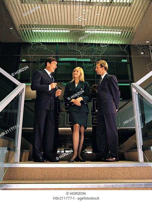Businesspeople discussing together while standing on staircase in United Kingdom, Europe