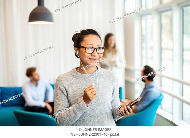 Young woman listening music while other friends sitting in background