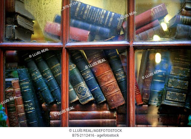 Old books stacked behind a window of a house in London, England, UK, Europe