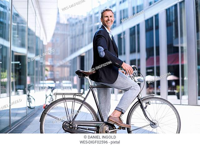 Smiling businessman on bicycle in the city