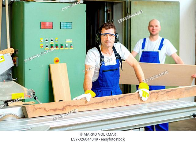 worker in a carpenter's workshop using saw machine