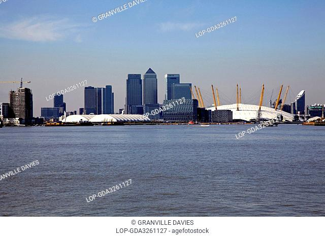 England, London, Greenwich Peninsula. Canary Wharf skyscrapers and the O2 formerly the Millennium Dome viewed from the River Thames