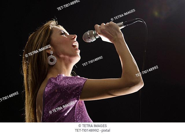 Woman singing in spotlight