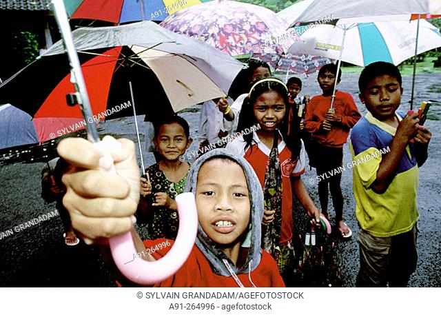Children holding umbrellas for tourists visiting Baths site. Tampaksiring. Bali Island. Indonesia