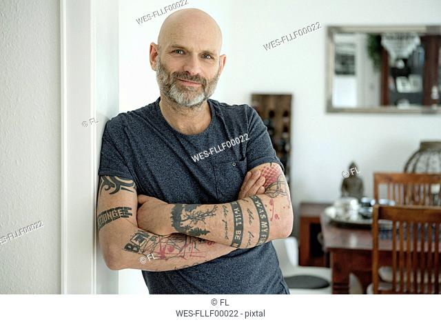 Tattooed man leaning in door of his home, with arms crossed