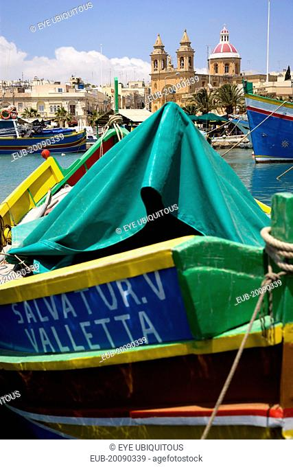 Fishing village harbour on the south coast with colourful Kajjiki fishing boats and the Church dedicated to Our Lady of the Rosary The Madonna of Pompeii